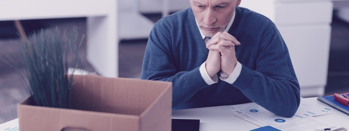 Man packing up his desk after being laid off