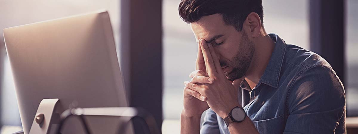 Man in front of computer distressed with hands resting on face