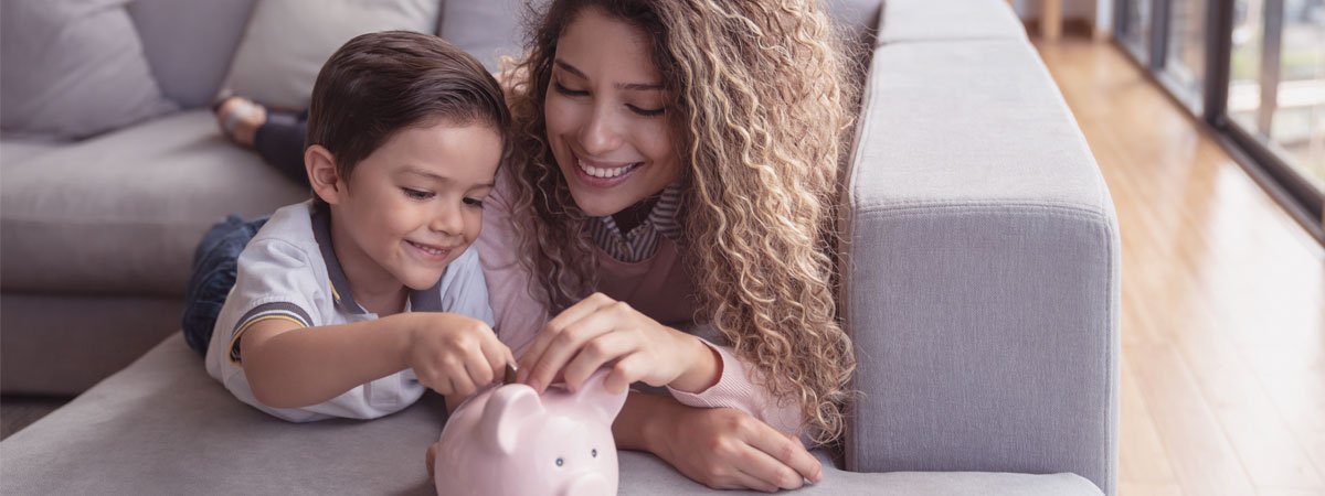 Mother and young son on the couch putting coins in a piggy bank.