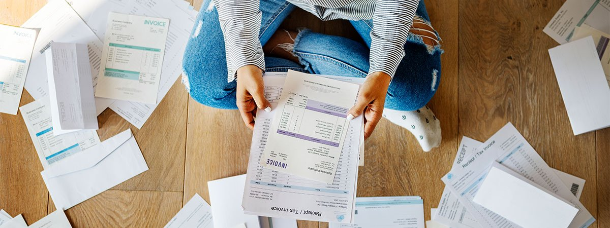 Person sitting on the floor overwhelmed by debt paperwork